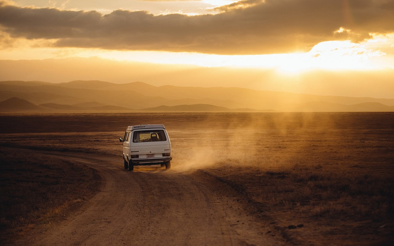 Car driving in the middle of a dusty road at dusk/dawn