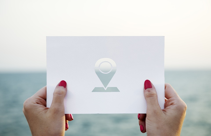 Woman's hands holding a location icon paper to show location