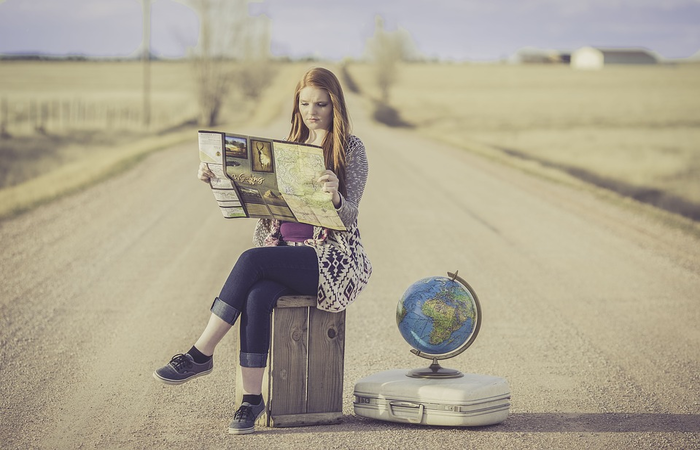 Woman sitting with a map in the middle of the road with attache and globe