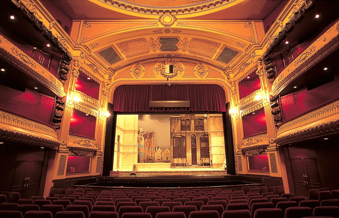 Stage with chairs and golden curtains